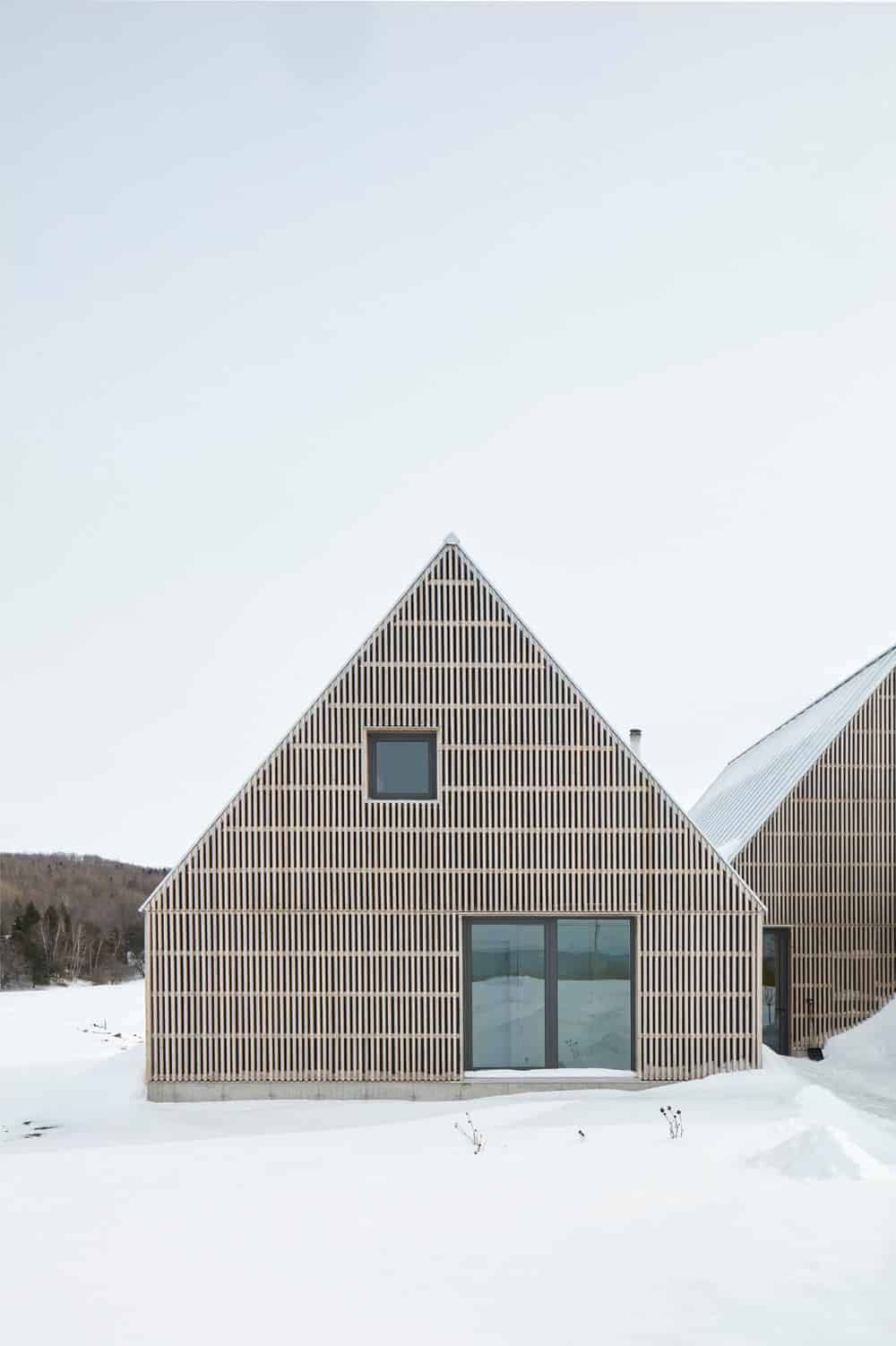 This is the facade of aScandinavian-Style home with a high Gable roof  paired with a small chimney on one side. The walls have a peculiar wooden slat design that offers an intricacy that contrasts the surrounding monotone of the white snowy scenery.