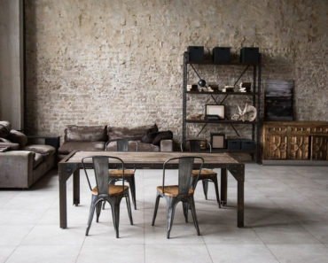 Industrial home decor with table, brick wall, tall ceilings and storage.