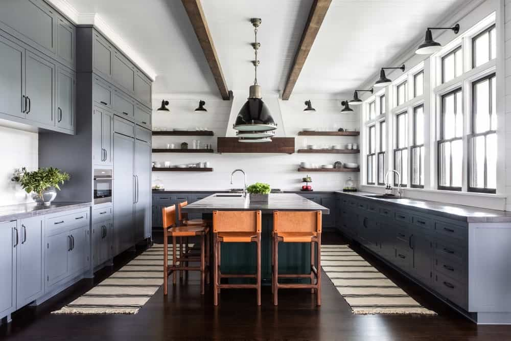 This brilliant and bright spacious kitchen has a couple of exposed wooden beams on its white ceiling that complements the gray shaker cabinets and drawers of the large L-shaped peninsula and its kitchen island in the middle of the dark hardwood flooring.