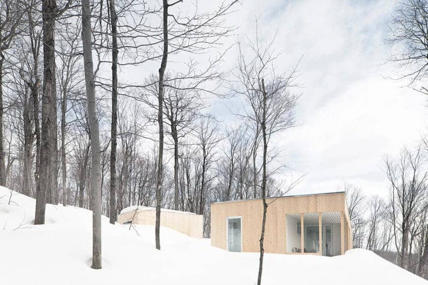 The straight lines and modern elements of this Scandinavian-Style house contrast with the feather-like bare branches of the forest surrounding it. The flat roof and abundant glass windows give this home a modern comfort in the middle of isolation.