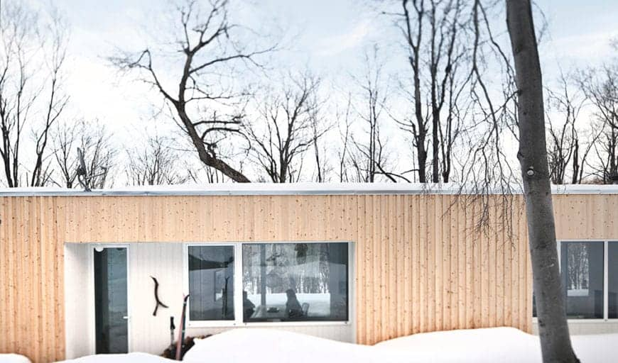 This is the facade of a Scandinavian-Style home that seems like a comfortable nest in the middle of a winter wonderland filled with naked dancing trees. The snowy landscape attempts to overwhelm but the beige walls of this flat-roofed home prevail.