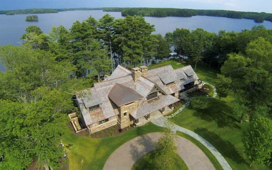 This aerial shot of the home allows for a better view of the surrounding lush greenery of the landscape that suits the lakeside terrain. The charming home is surrounded by well-maintained grass and tall trees. There is also on tall tree in the middle of the circular driveway in front of the house.