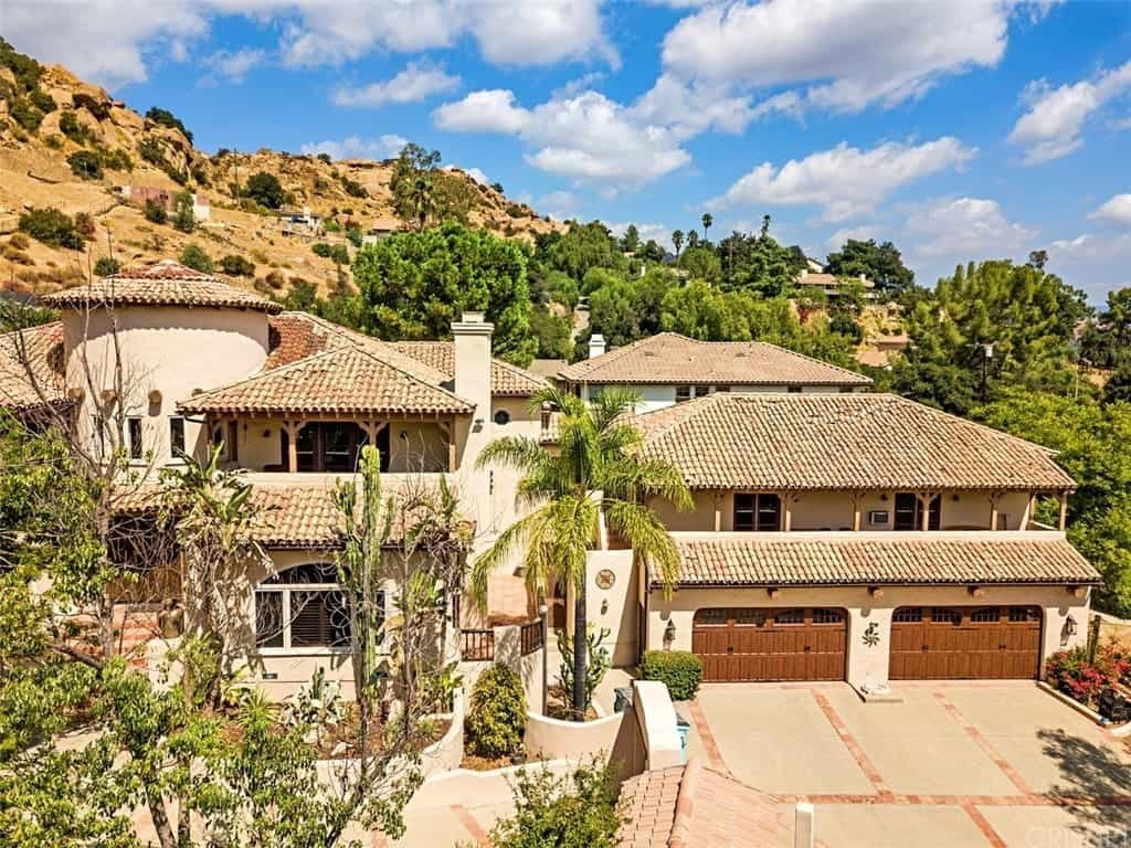 This expansive Southwestern-style home has brick-colored roofing clay tiles on its various roof tops that complement the beige exterior walls for that classic look. There is a couple of wide wooden garage doors amounting to a garage that can fit at least four vehicles.