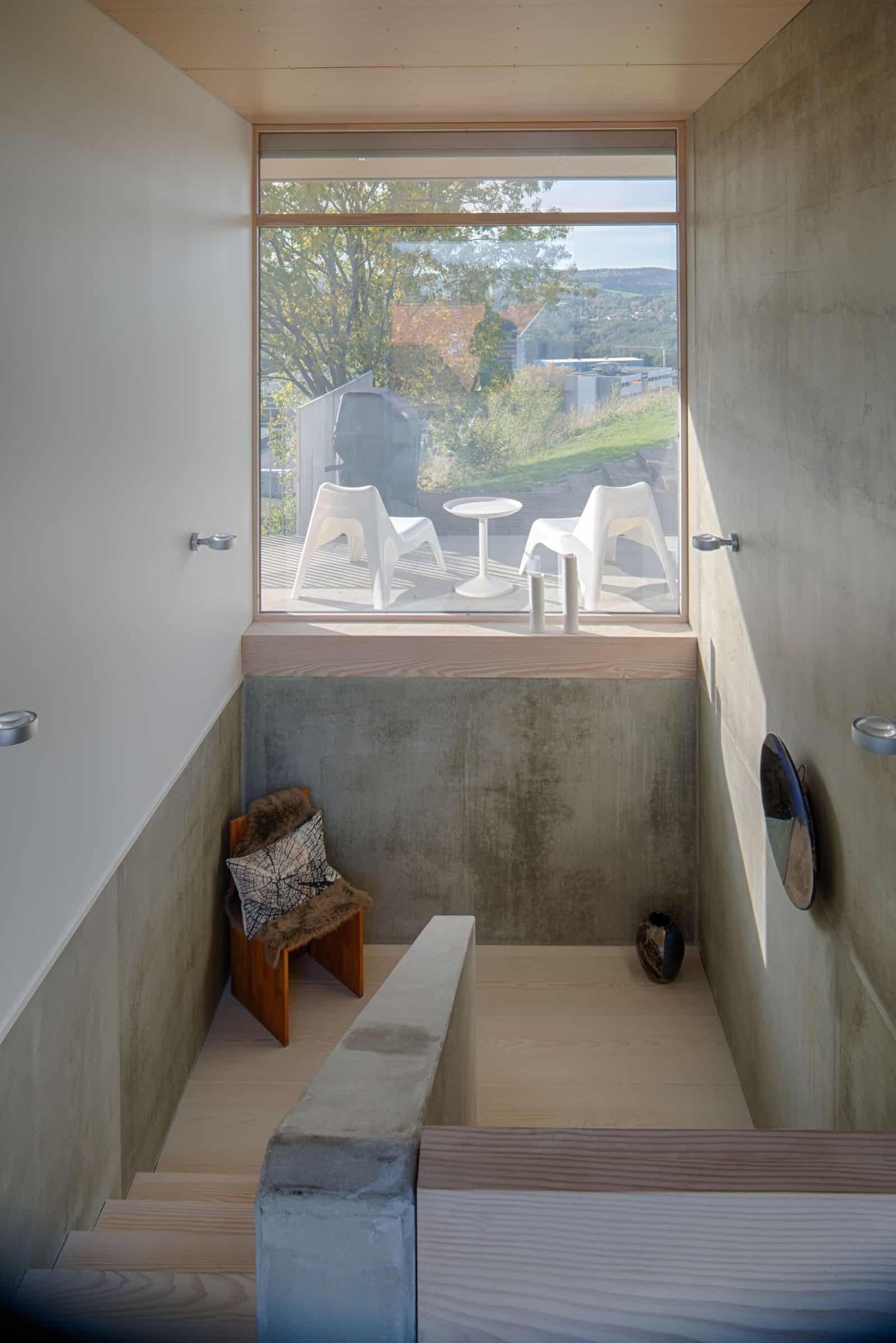 Typical landing with concrete handrail, small chair and a fixed glass window, giving access to natural light.
