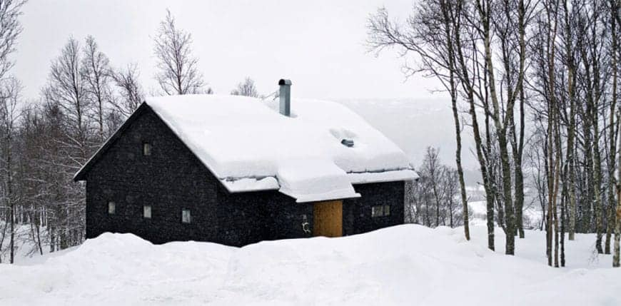 This Scandinavian-Style home presents with dark wooden walls that stand in contrast with the surrounding frozen tundra. It represents a warm embrace that is welcoming and hospitable from the surrounding harsh weather.