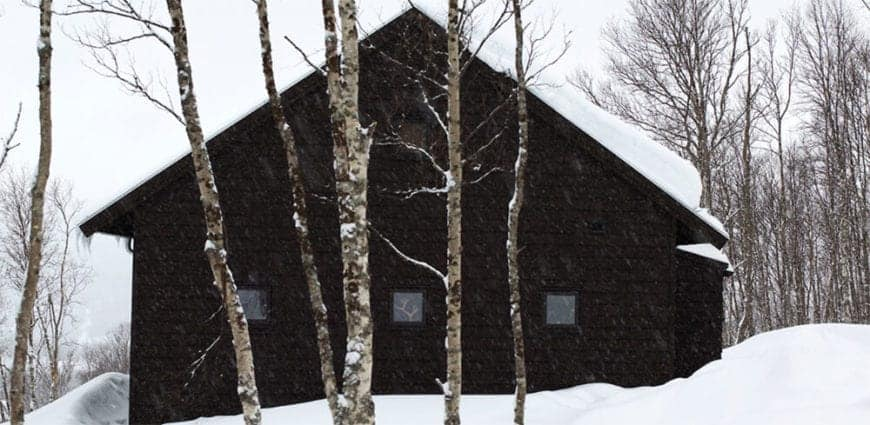 This charming dark house in the middle of a frozen tundra has Gable roofing paired with small square windows for a modern effect. It is a beacon of rest and reprieve from the tundra but at the same time incorporates the beauty of its surrounding to the welcome it gives you.