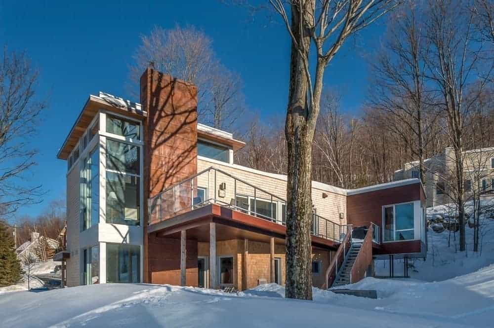 This Scandinavian-Style home has a proud slab of stone wall rising up with the tall trees. This wall earthen wall supports the rest of the modern house's flat roofing, immense glass walls and a balcony on the side with a set of stairs leading to the snowy landscape.