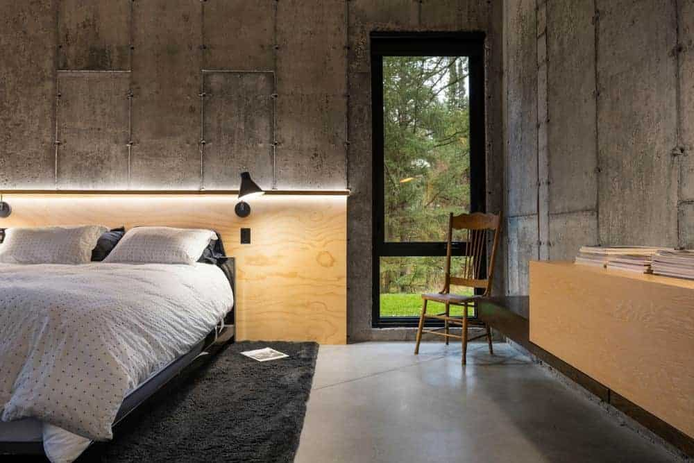 The concrete flooring that is covered with a black area rug matches with the upper layer of the gray concrete walls. The lower half of it is dominated by light wooden structures like the headboard and the floating cabinet on the adjacent wall.