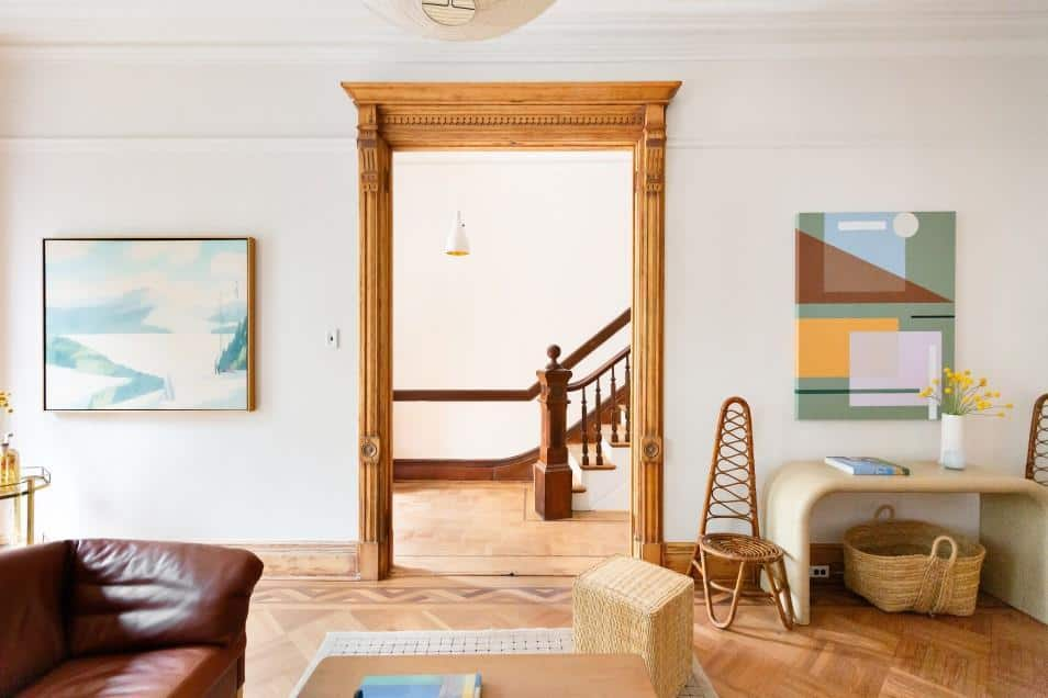 This entry hall has a simple Scandinavian-Style design with a hardwood flooring separated from the white walls by wooden moldings that match the wooden railings and steps of the staircase leading to the second floor. This area is illuminated by a white modern pendant light.