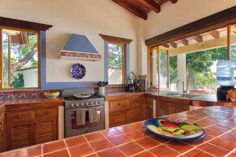 Southwestern style kitchen with mosaic tiles, rustic tile countertop, and plenty of windows to appreciate the natural outdoors.