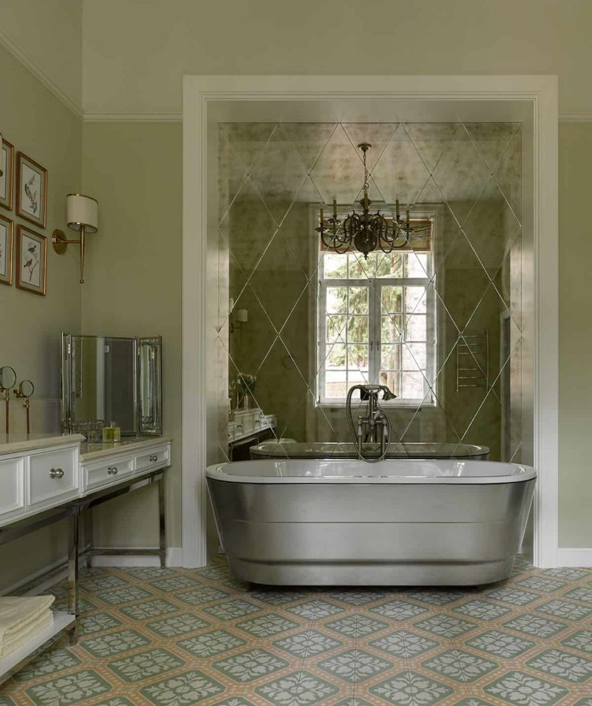 The brilliant silvery freestanding bathtub is the highlight of this bathroom that has light green patterned floor tiles that match the beige countertop of the vanity area that has green walls adorned with framed artworks and wall-mounted lamps.