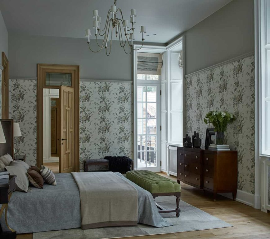 This charming traditional bedroom has green floral walls that serve as a nice background for the wooden dresser that complements the hardwoode flooring. There is a light gray area rug underneath the gray bed with a green cushioned bench at the foot of the bed.