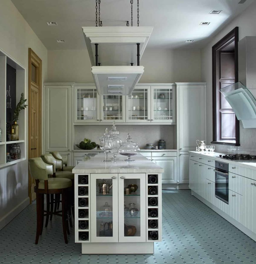 This traditional kitchen has pastel green patterned floor tiles that contrasts the white wooden shaker cabinets and drawers that blend in with the white walls and ceiling where a shelf hangs over the white kitchen island.