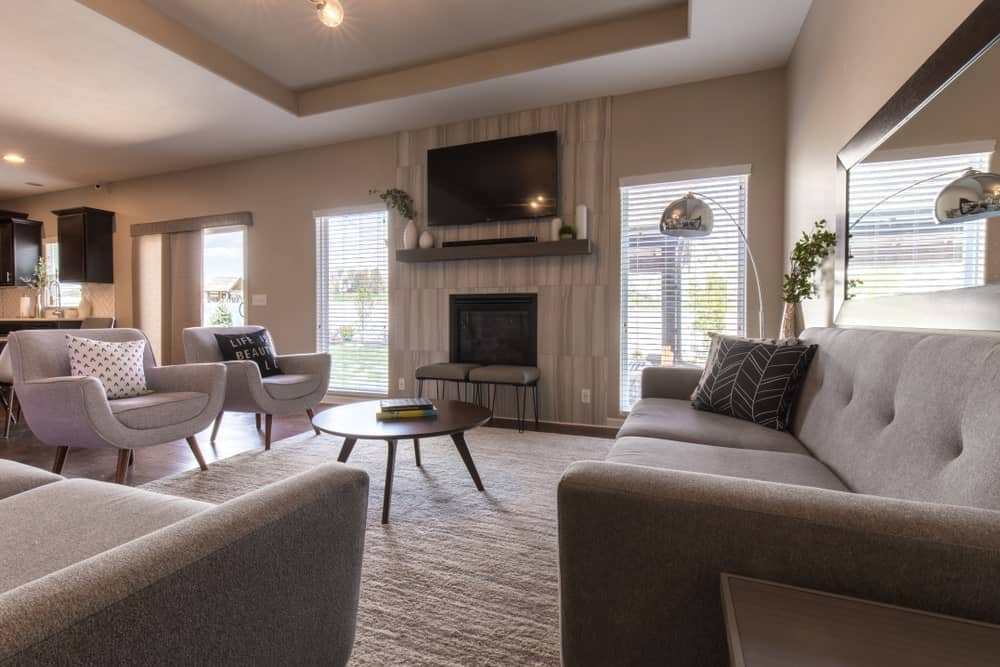 Transitional-style living room with tray ceiling, ledge shelving, a fireplace, and an area rug.