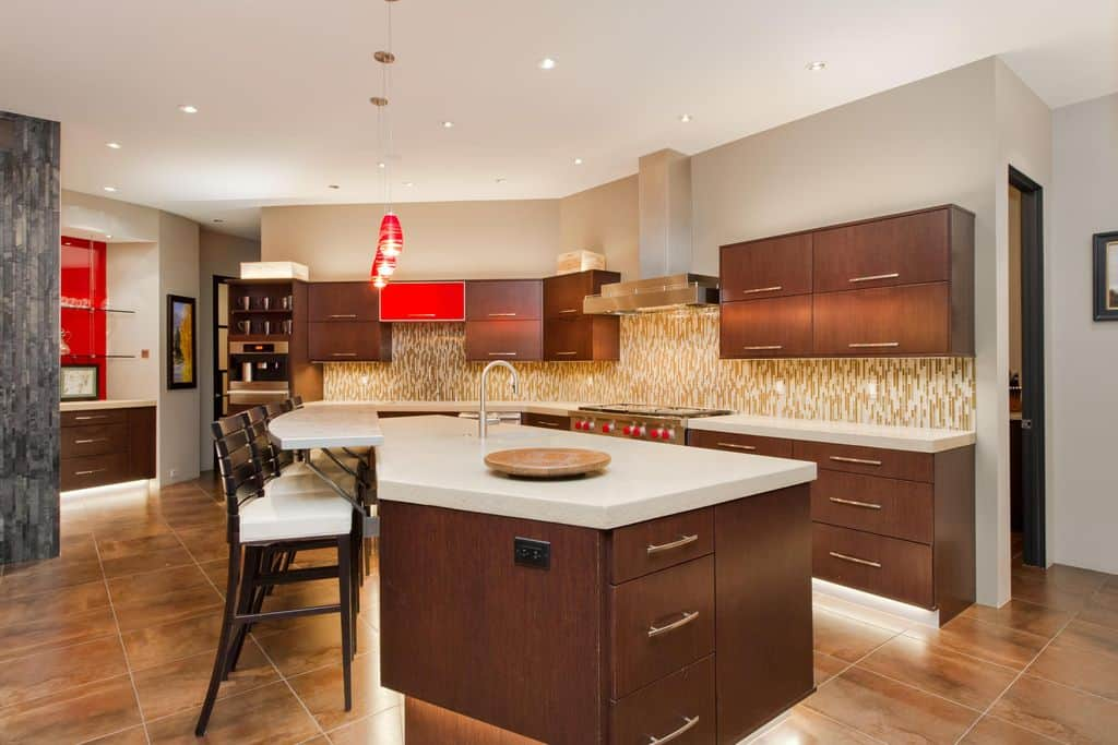 Fabulous kitchen boasts dark wood cabinetry that matches with breakfast bar fitted with a raised eating counter that's lined with white cushioned stools. There's a pop of red from the pendant lights and one kitchen cabinet.