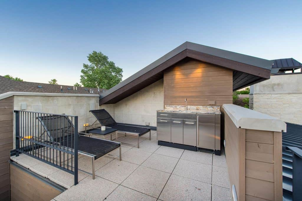 This outdoor kitchen offers a couple of loungers set on the home's rooftop.