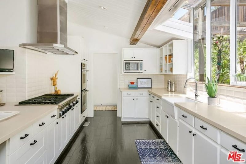 White kitchen featuring espresso-finished hardwood flooring and a white shed ceiling with an exposed beam.