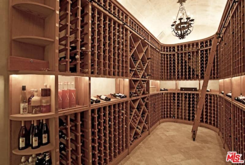 A sophisticated wine cellar featuring redwood racks accented with diamond patterned shelves. It includes an elegant chandelier and herringbone tiled flooring.