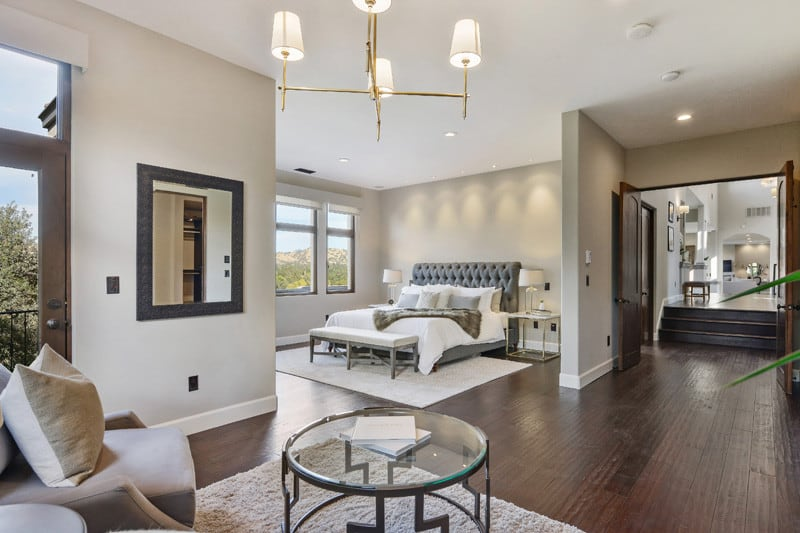 This regal space comprises some wonderful modern fixtures. This includes a simple square-framed mirror, artistic chandelier and a glass coffee table. The wooden floor panels and the muted tones of the walls give it a stately look. While the soft cushioned sofa and the luxurious bed make sure that this noble abode doesn't miss out on comfort.