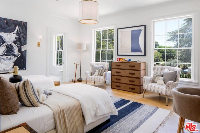 White modern guest room with contrasting colors from a wall painting, multi-colored carpet and lovely furniture.