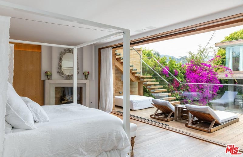 This primary bedroom showcases a frameless window covered with a sheer curtain and overlooking the balcony. It has a canopy bed over wood planked flooring.