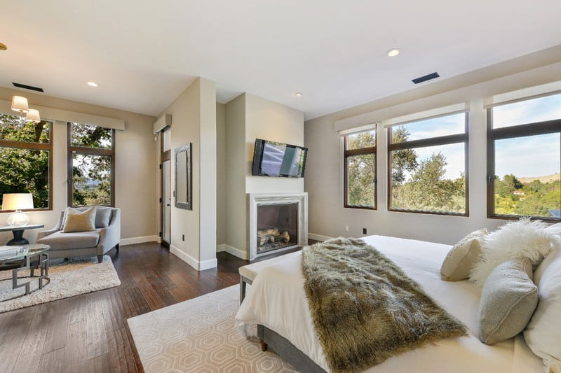 A large master bedroom with a fireplace and a sitting area near the windows. The room features hardwood floors topped by rugs.
