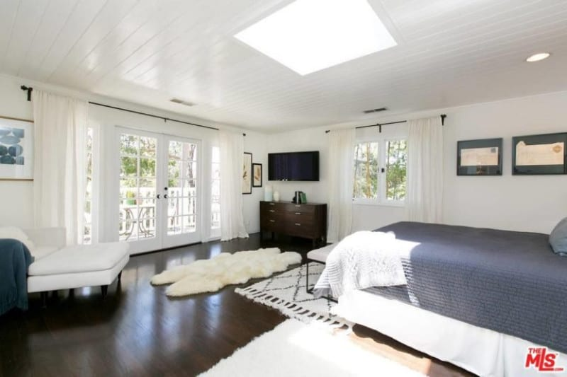 Spacious master bedroom featuring area rugs covering the hardwood flooring together with white walls and ceiling with a skylight.
