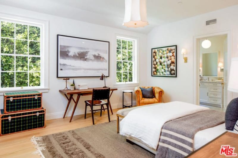 Beautifully designed mid-size guest room with traditional features including carpeted bed space, white walls, shabby-chic solo seat, interesting wall framed photos and elegant bell-shape lighting.