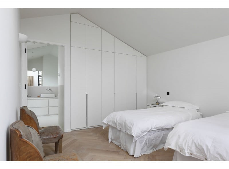 White bedroom with herringbone pattern flooring and vaulted ceiling.