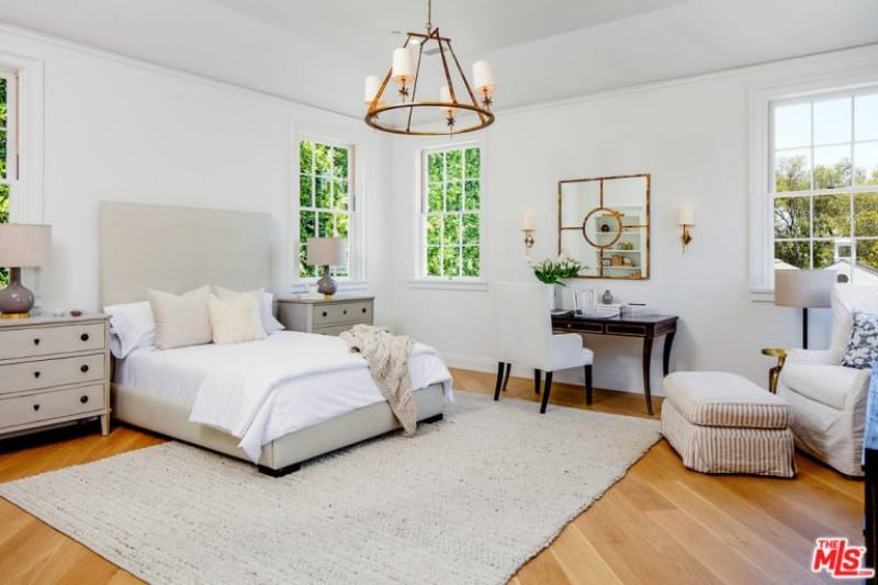 Rustic chandelier, vanity, light wooden floor and comfy-chic furniture perfectly complement this white guest bedroom.