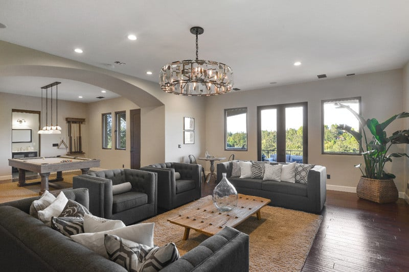 This living room offers a stylish gray sofa set lighted by a glamorous chandelier. The hardwood flooring looks perfect together with the beige walls.