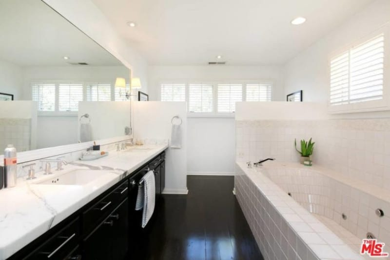 Another black and white themed bathroom, this one sets itself apart by using almost brick like patterns for its tub. The large mirror and windows help to reflect light and make the narrow space seem wider. The black tiles and cupboard are sleek and non-fussy, making the design effortlessly stylish.