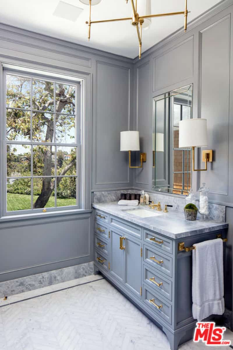 Gray shade goes well with this elegant bathroom of Lindsey. The whole design looks refreshing with wooden walls that matched the zigzag tile really well. The brass lighting fixtures and a huge double-hung window accentuated the room.