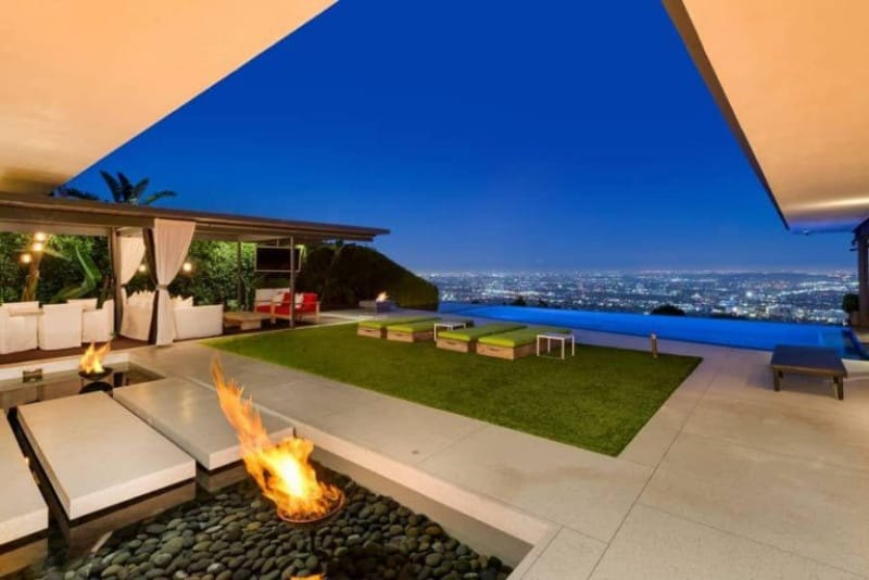 This luxurious outdoor area features a beautiful lawn area along with the patio and outdoor dining.