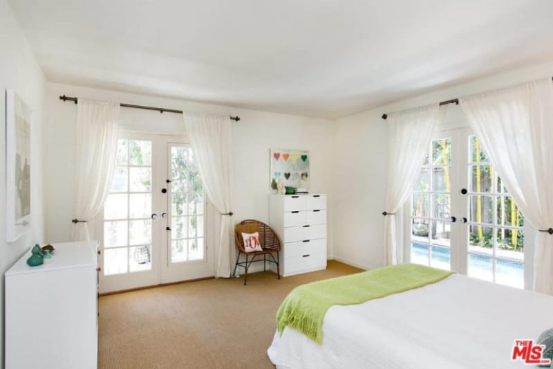 This calm, white colored palette carpeted bedroom is a perfect place to relax enjoying the natural access of lighting from the double glass door entry.