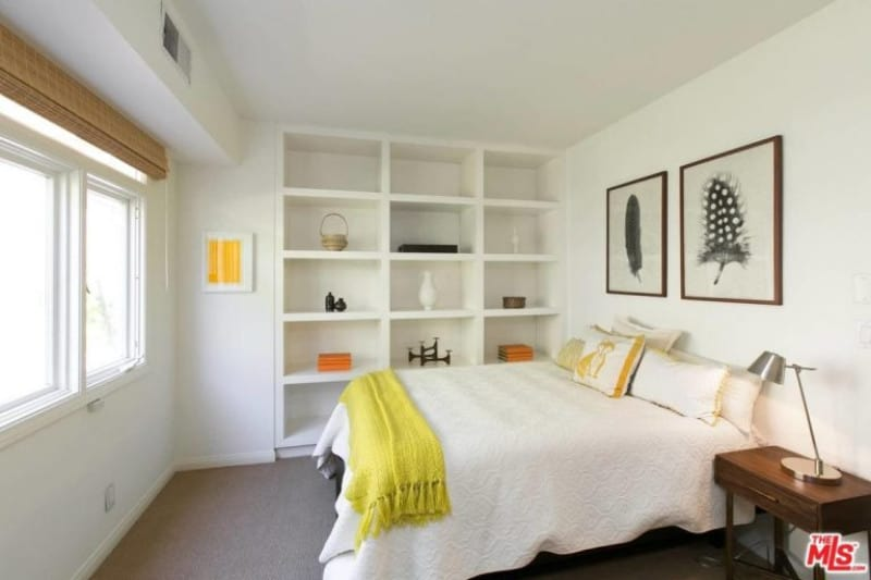 Neutral toned bedroom with white walls, carpeted floor and shelves left open around figurines.