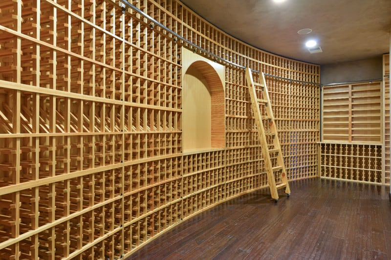 Curved wine cellar with empty wooden racks highlighting an arched shelf in the middle. It is lined with a matching wooden ladder with steel railings.
