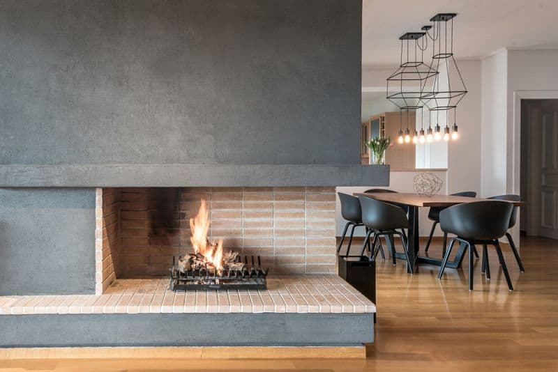 An open brick fireplace fixed to the charcoal wall in this dining area featuring industrial pendant lights that hung over a wooden dining table and black round back chairs.