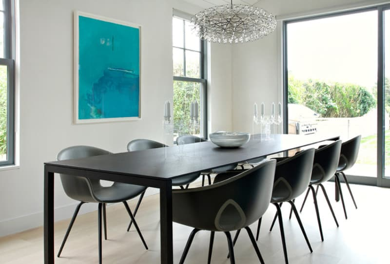 A fancy chandelier illuminates the black dining set in this dining room. It is designed with a blue wall art canvas mounted on the white wall.