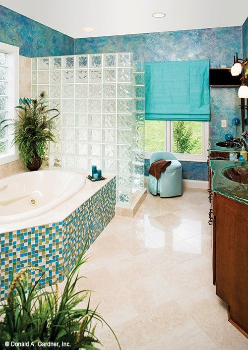 Primary bathroom with striking blue walls, double vanities with distressed counters, a soaking tub clad in blue mosaic tiles, and a walk-in shower enclosed in glass block panels.