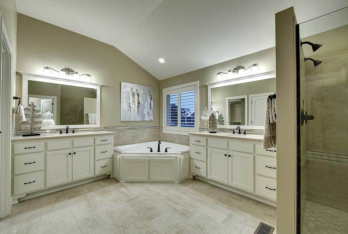 This is a spacious bathroom with a corner bathtub in between the two light beige vanities that pair well with the flooring and walls.
