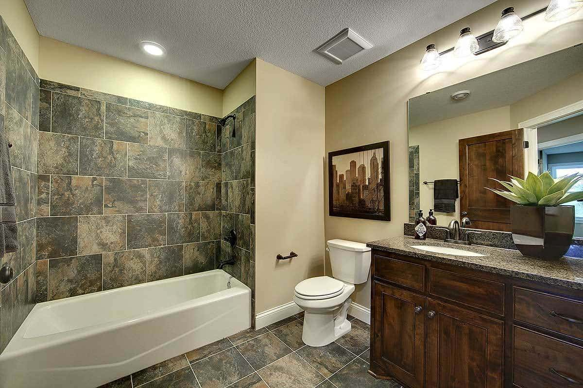 The shower area beside the toilet has gray marble tiles on its walls to match the flooring that complements the dark wooden vanity that is topped with a wall-mounted lamp.