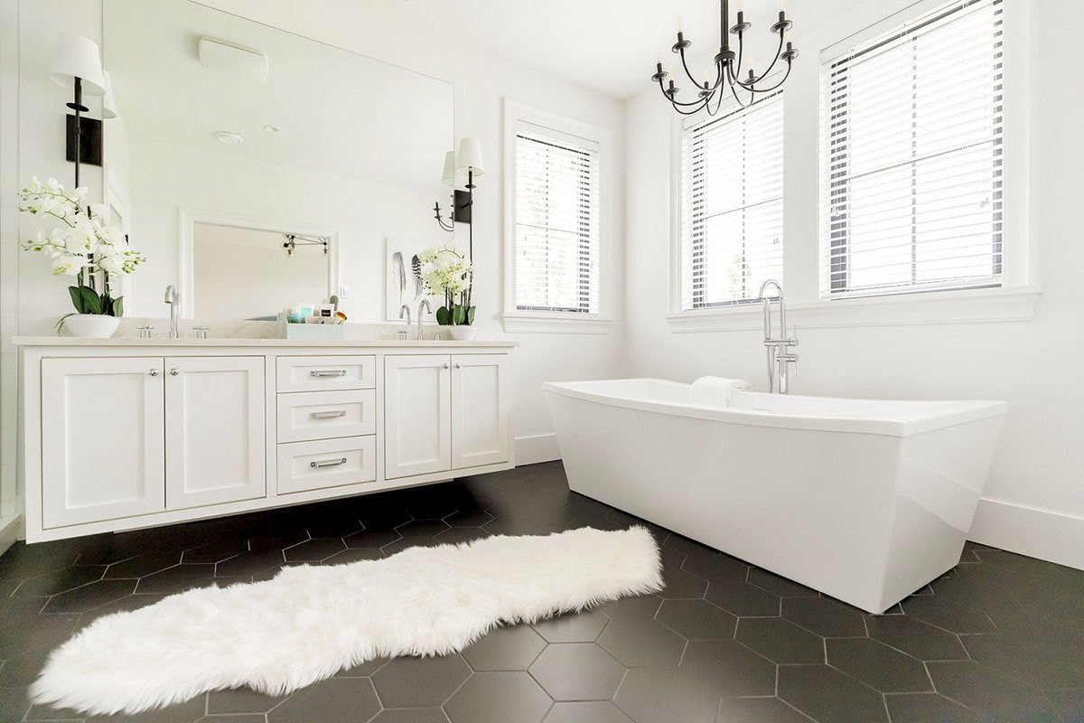 The black hex tile flooring sets a nice contrast to the stark white walls, floating vanity, freestanding tub, and faux fur rug in this primary bathroom.
