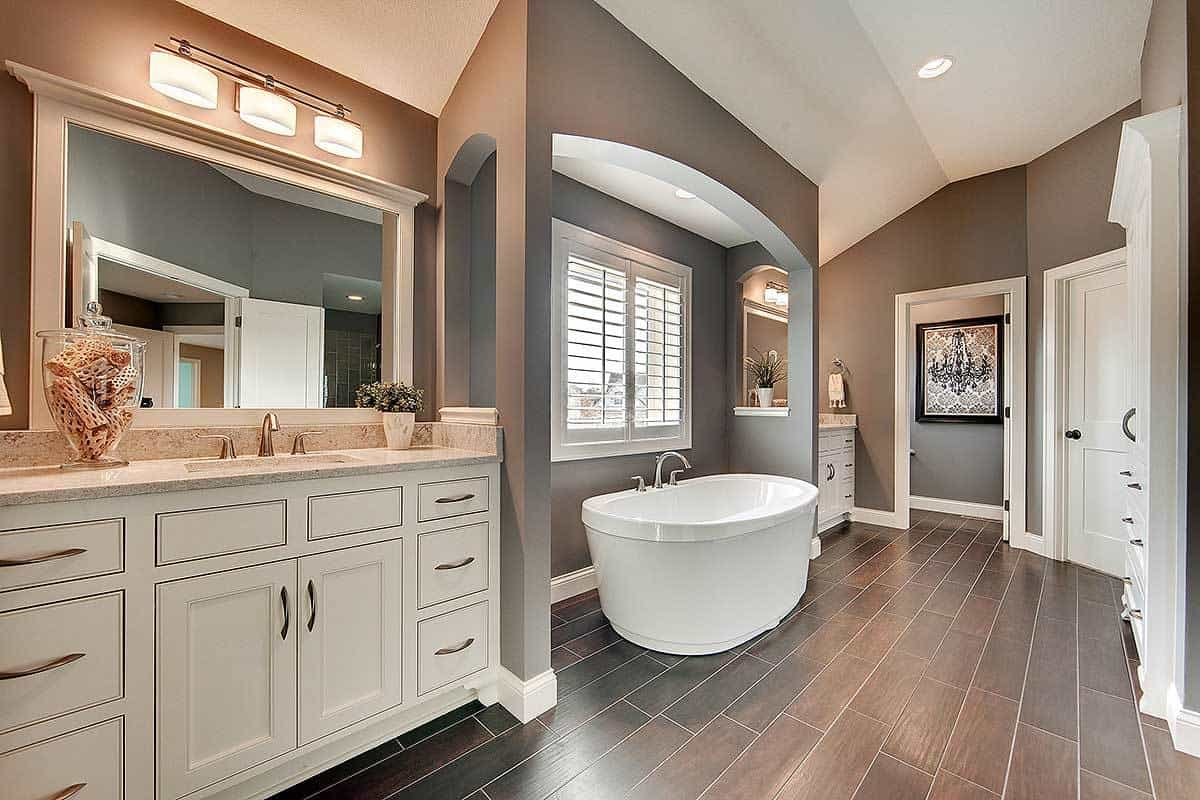 The primary bathroom has a freestanding bathtub placed under an arch and a shuttered window. This is in between the two vanities with its own beige cabinets, wall-mounted mirror, and lamps.