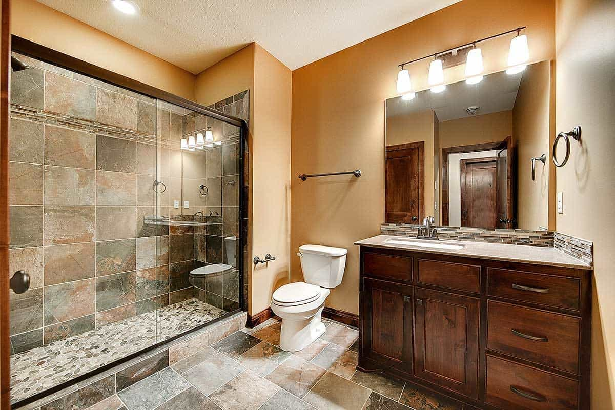The other bathroom has a small dark wooden vanity, toilet and a glass-enclosed walk-in shower area with various gray marble-like tiles to match the flooring of the bathroom.