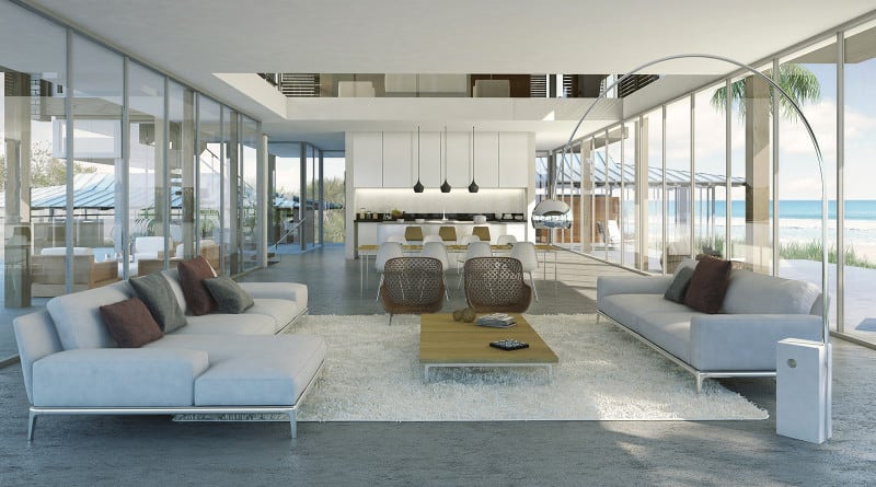 Spacious beachside mansion living room with light gray furniture, floor-to-ceiling windows in large open space.