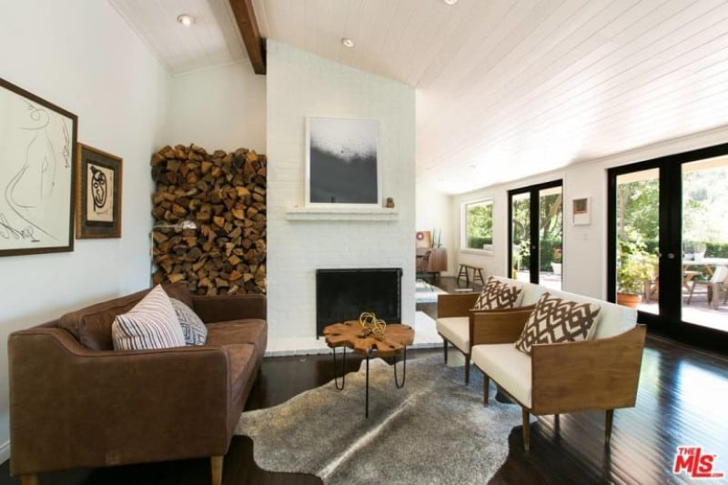 White living room offers brown couch and white armchairs paired with a wooden coffee table across the fireplace fixed to the white pillar with firewoods on the side.