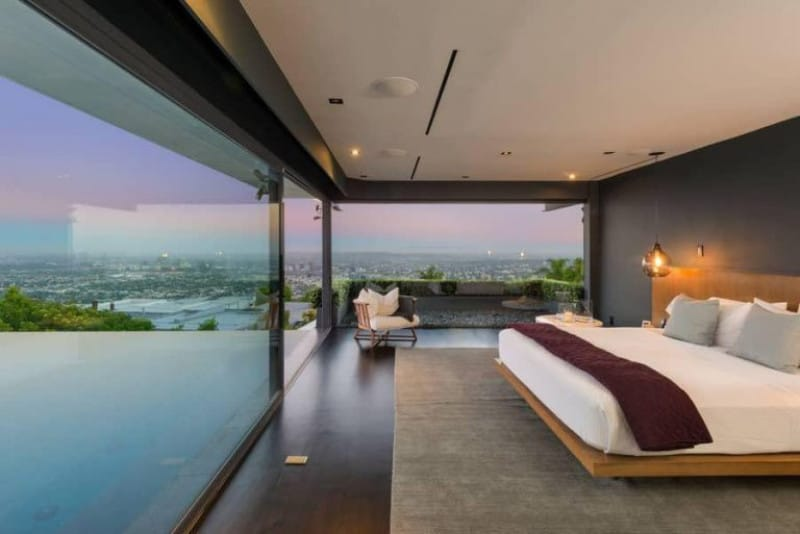 Modern primary bedroom surrounded by floor to ceiling windows with a breathtaking view. The bed is lighted with a glass pendant and sits on a gray rug.