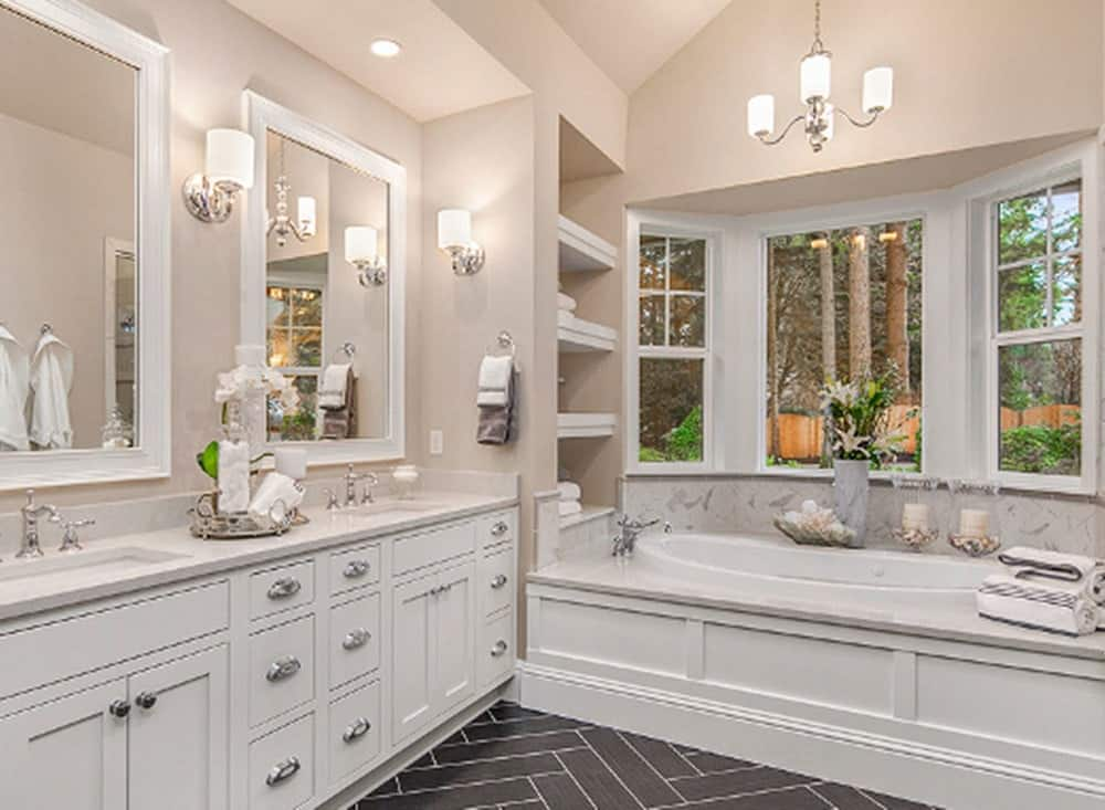 The black herringbone tiles of the floor gives a wonderful contrast to the white cabinetry of the vanity that matches well with the housing of the bathtub.