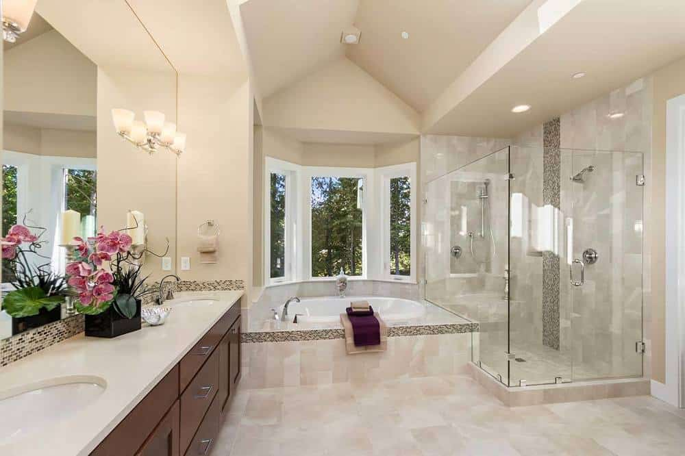 This luxurious bathroom has a small bathtub in the middle of the glass-enclosed shower area and the dark brown wood vanity. These are then complemented by the beige flooring that extends to the house of the bathtub.